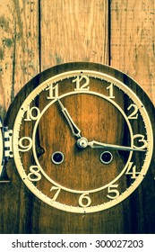 Retro clock on wooden wall background. Concept of the passage of time.