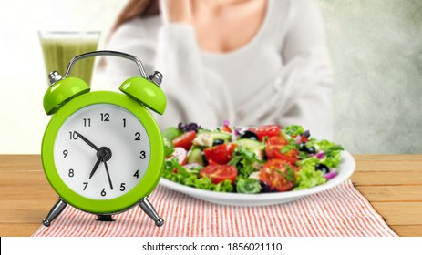 Retro clock in which woman make Intermittent fasting with a Healthy food of salad.