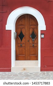Retro closed wooden door entrance with white arch on the top
