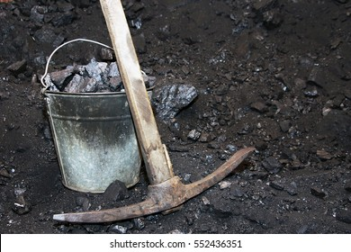 Retro coal mining. Pickaxe and the bucket with coal in mine