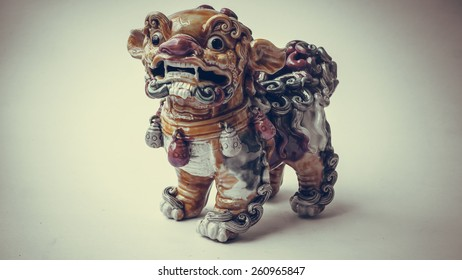 Retro color ceramic ancient lion mythical creature statue. Symbol of luck and prosperity for chinese and asian sculpture. Slightly defocused and close-up shot. Copy space.