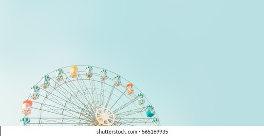 Retro colorful ferris wheel of the amusement park in the blue sky  background.