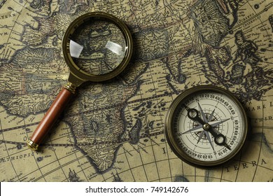 Retro compass with old map and magnifier
