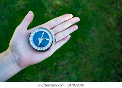 Retro compass on man's hand on trail during hiking. Grass as a blurred background
