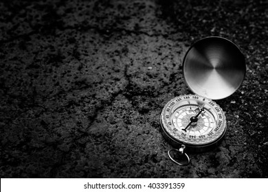 Retro compass on road texture background, black and white tone, journey of life concept