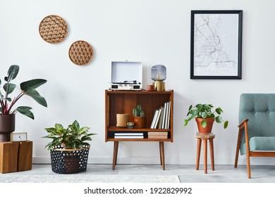 Retro composition of living room interior with mock up poster map, wooden shelf, book, armchair, plant, cacti, vinyl recorder, decoration and personal accessories in stylish home decor. - Shutterstock ID 1922829992