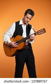 Retro country male guitar player wearing black suit. Studio shot.