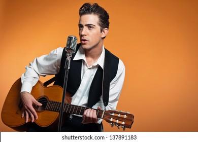 Retro country singer with guitar wearing black suit. Studio shot.
