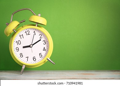 Retro dancing alarm clock on wooden board with green background
