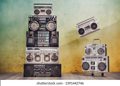 Retro design ghetto blaster boombox cassette tape recorders towers from 1980s on handcart front concrete wall background conceptual composition with flying radio. Vintage old style filtered photo