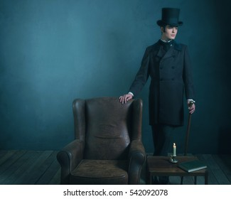 Retro dickens style man standing with cane next to leather chair.