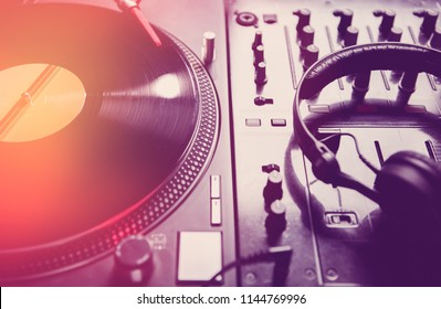 Retro dj turntable player with vinyl analog disc.Vintage record with music on turn table.Sound mixer with professional headphones for playing music on concert in night club.Techno djs stage equipment