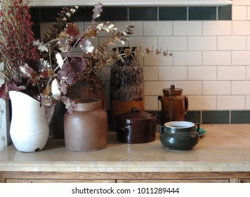 Retro earthen ware ceramics and enamel vessels, jug, vase, bowl, canister, pot, with foliage vignette on kitchen bench with subway tile splash back