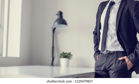 Retro effect faded and toned image of a businessman standing in office with his hands in the pockets of his suit pants.