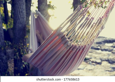 Retro effect faded and toned image of a person relaxing in a hammock in the shade of a tree on a shoreline viewed from behind.