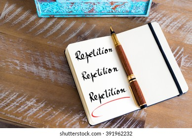Retro effect and toned image of a fountain pen on a notebook. Handwritten text Repetition, Repetition, Repetition as business concept image