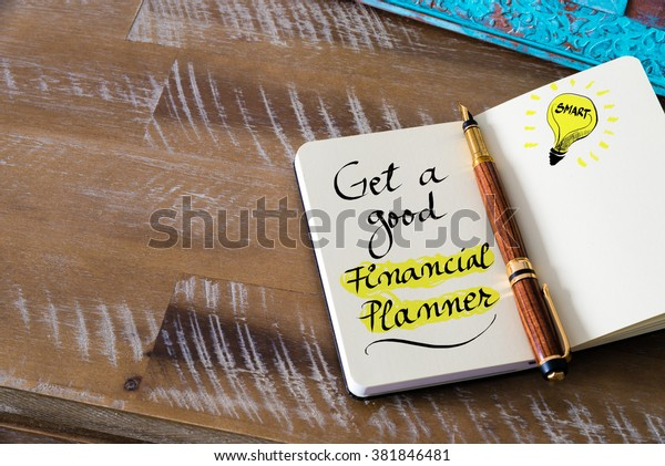 Retro effect and toned image of notebook next to a fountain pen. Business concept image with handwritten text GET A GOOD FINANCIAL PLANNER, copy space available, light bulb as smart idea