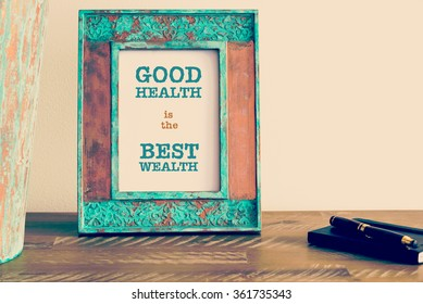 Retro effect and toned image of a vintage photo frame next to fountain pen and notebook . Motivational quote written with typewriter font GOOD HEALTH IS THE BEST WEALTH