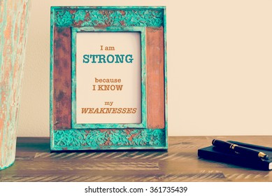 Retro effect and toned image of a vintage photo frame next to fountain pen and notebook . Motivational quote written with typewriter font I AM STRONG BECAUSE I KNOW MY WEAKNESSES