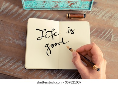 Retro effect and toned image of a woman hand writing a note with a fountain pen on a notebook. Motivational concept with handwritten text LIFE IS GOOD