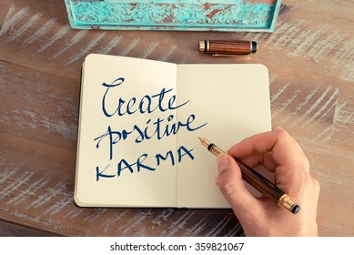 Retro effect and toned image of a woman hand writing a note with a fountain pen on a notebook. Motivational concept with handwritten text CREATE POSITIVE KARMA