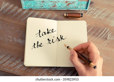 Retro effect and toned image of a woman hand writing a note with a fountain pen on a notebook. Motivational concept with handwritten text TAKE THE RISK