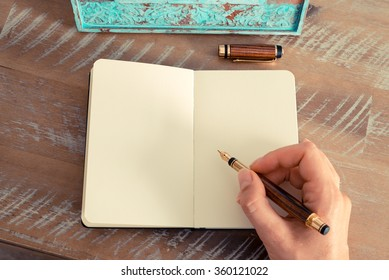 Retro effect and toned image of a woman hand writing a note with a fountain pen on a notebook. Copy space available