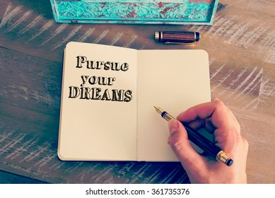 Retro effect and toned image of a woman hand writing a note with a fountain pen on a notebook. Motivational message PURSUE YOUR DREAMS as concept for self improvement