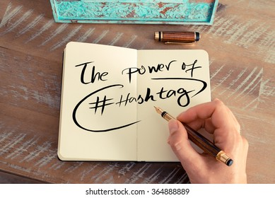 Retro effect and toned image of a woman hand writing a note with a fountain pen on a notebook. Handwritten text THE POWER OF HASHTAG, business success concept