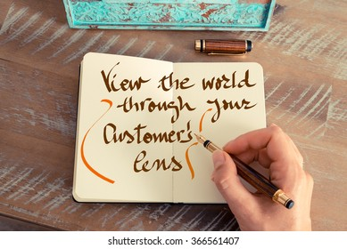 Retro effect and toned image of a woman hand writing a note with a fountain pen on a notebook. Handwritten text VIEW THE WORLD THROUGH YOUR CUSTOMER LENS, business success concept