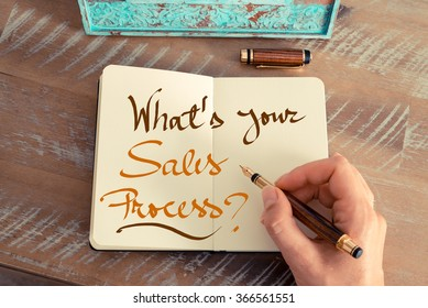 Retro effect and toned image of a woman hand writing a note with a fountain pen on a notebook. Handwritten text WHAT'S YOUR SALES PROCESS ?, business success concept