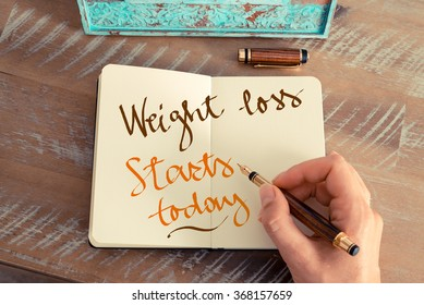Retro effect and toned image of a woman hand writing a note with a fountain pen on a notebook. Handwritten text WEIGHT LOSS STARTS TODAY, motivation concept