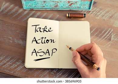 Retro effect and toned image of a woman hand writing a note with a fountain pen on a notebook. Handwritten text Take Action ASAP as business concept image