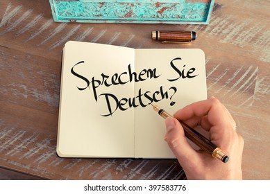"Retro effect and toned image of woman hand writing a note on a notebook. Handwritten text ""Sprechen Sie Deutsch?"" in German - translation : Do you speak German? as business concept image"