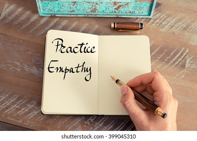 Retro effect and toned image of a woman hand writing a note with a fountain pen on a notebook. Handwritten text Practice Empathy as success and evolution concept image