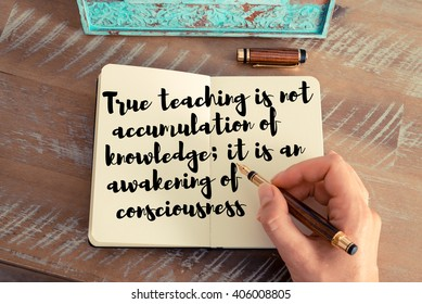 Retro effect and toned image of a woman hand writing on a notebook. Handwritten quote True teaching is not accumulation of knowledge; it is an awakening of consciousness as inspirational concept image