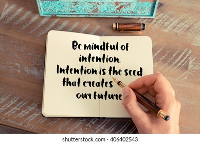 Retro effect and toned image of a woman hand writing on a notebook. Handwritten quote Be mindful of intention. Intention is the seed that creates our future.  as inspirational concept image