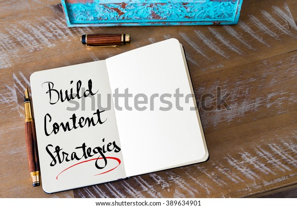 Retro effect and toned image of a woman hand writing a note with a fountain pen on a notebook. Handwritten text Build Content Strategies as business concept image
