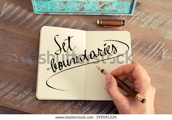 Retro effect and toned image of a woman hand writing a note with a fountain pen on a notebook. Handwritten text Set Boundaries as success and evolution concept image