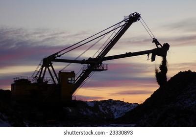 Retro excavator in open cast mining quarry