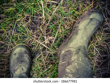 Retro Faded Photo Of Dirty Rubber Boots In The Countryside