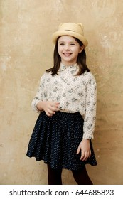 retro fashion. adorable, small, little girl or stylish young model, with brunette hair in fashionable hat with ears, shirt and skirt, posing on white wooden shutters. Child fashion