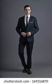 Retro fashion fifties young man wearing dark suit and tie. Studio shot against grey.