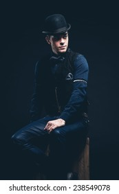 Retro fashion man with blue shirt, gilet, jeans and bow tie. Wearing black hat. Sitting on vintage wooden box. Studio shot against black.