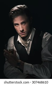 Retro fashion young man with glass of whiskey in waistcoat. Greasy Hair combed back. Dark blue background.