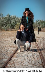 Retro fashionable woman and man standing on railroad in vintage style of old town, Girl wearing coat and hat for cold windy weather standing behind her man