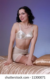 0fb8572b62 Retro fifties pin-up attractive girl in vintage satin bra and girdle in  boudoire