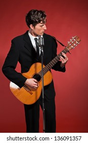 Retro fifties rock and roll singer playing acoustic guitar. Studio shot.