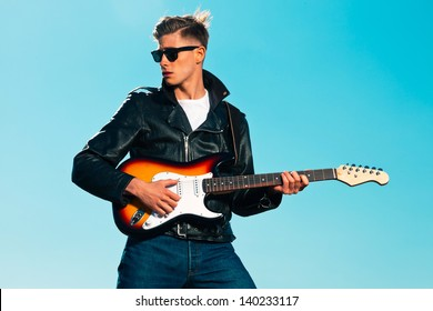 Retro fifties rockabilly electric guitar player wearing black leather jacket. Blue sky.