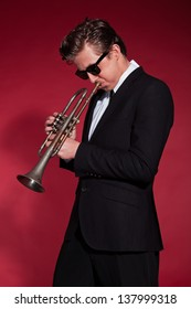 Retro fifties trumpet player wearing black suit and sunglasses. Blowing trumpet. Red wall.